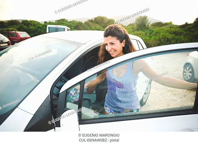 Happy woman getting into car at the coast