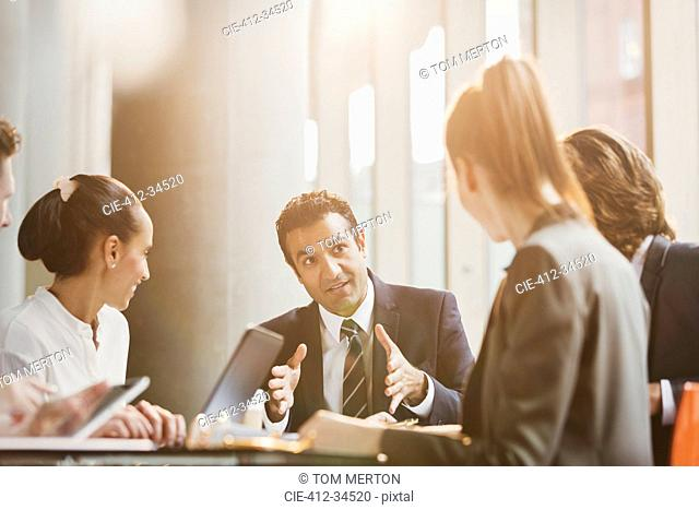 Businessman talking, leading conference room meeting