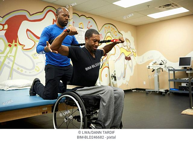 Physical therapist helping man in wheelchair strengthen arms