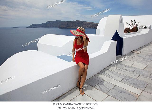 Woman sitting at the cliff looking down to Caldera, Oia town, Santorini, Cyclades Islands, Greek Islands, Greece, Europe