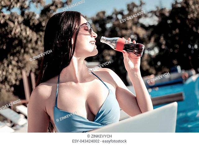 Holidays time. Side view on a positive minded brunette grinning broadly while drinking a glass bottle of sparkling water while sunbathing in summer
