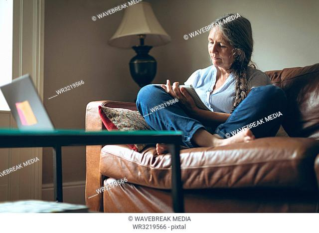 Senior woman writing on a notepad in living room