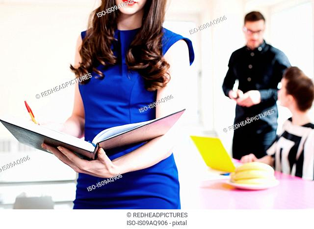 Woman wearing blue dress holding book