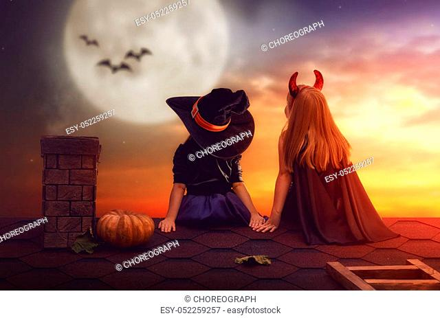 Two happy sisters on Halloween. Funny kids in carnival costumes sitting on the roof. Cheerful children looking at moon