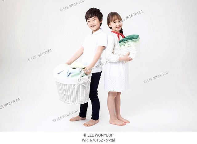 a boy and a girl carrying laundry