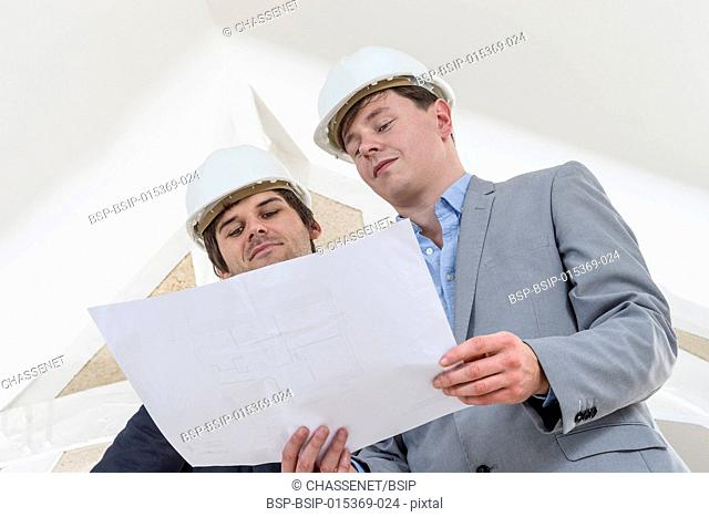 Two Engineer or Architect discuss on Project at Construction site in white environment