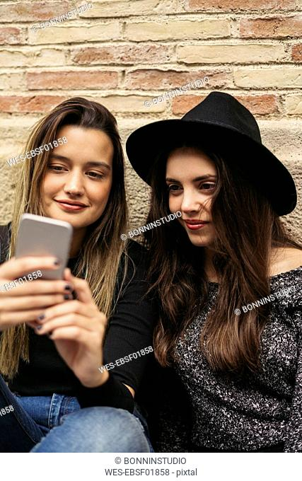 Two best friends looking at smartphone