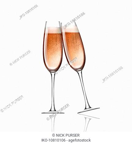 Two pink champagne in flutes toasting on white background