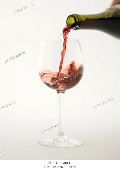Red wine pouring into grass, white background