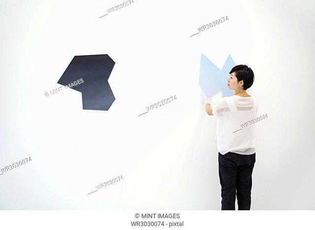 Woman with short black hair wearing white shirt hanging modern painting on white wall in art gallery