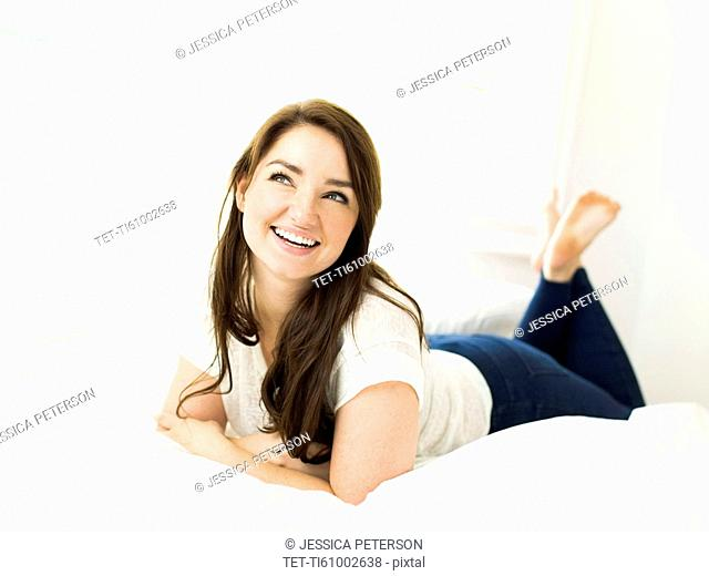 Portrait of woman lying on bed and smiling