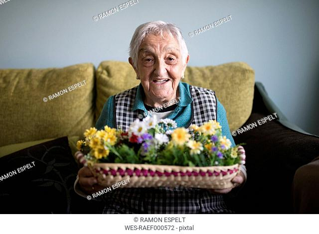 Portrait of senior woman showing a basket decorated with artificial flowers