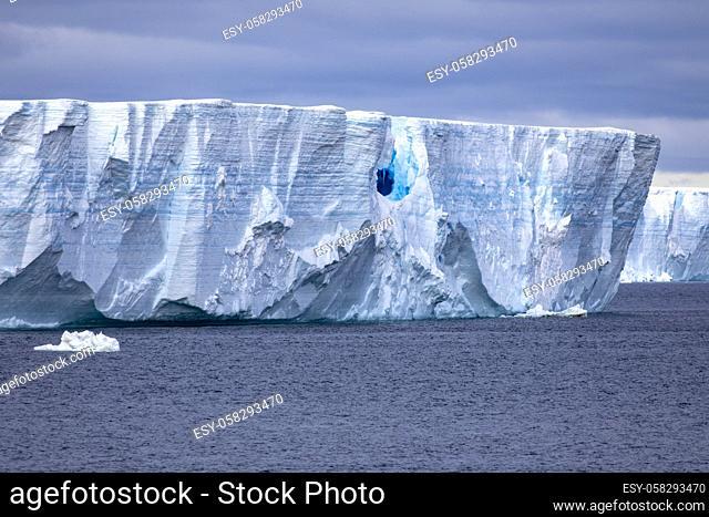 Dark blue iridescent ice caves in gigantic iceberg floats in Arctic Ocean