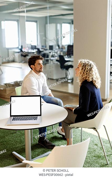 Two colleagues talking in office with laptop on table