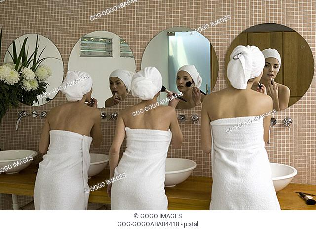 Women wrapped in towels applying makeup