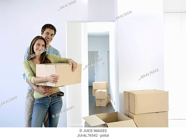 Portrait of a young couple moving in to a new house