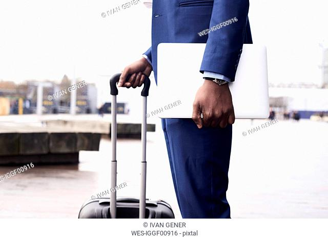 Waiting businessman with laptop and trolley bag wearing blue suit, partial view