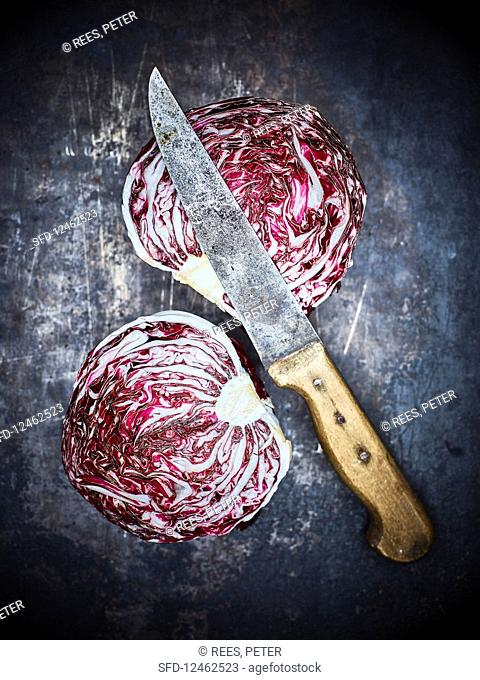 A halved radicchio with a kitchen knife on a dark metal background