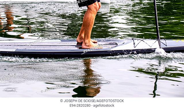 Partial view of a young man's legs standing on a paddle board on a lake