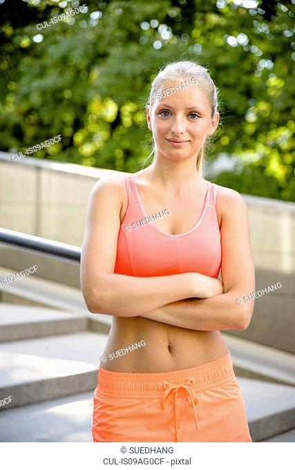 Portrait of young female runner with arms folded