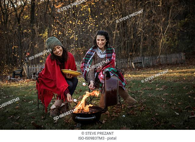 Two female friends toasting marshmallows on campfire