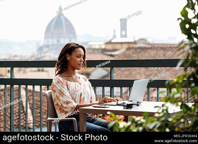 Young woman using laptop on a balcony in Florence, Italy