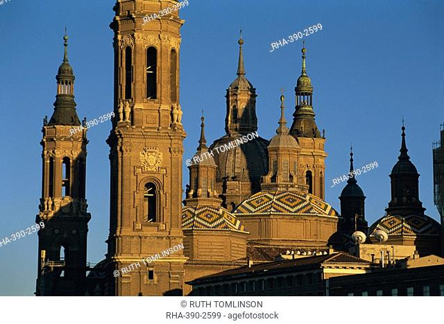 The towers, spires and tiled roogs of the Basilica of Nuestra Senora del Pilar at sunset, Zaragoza, Aragon, Spain, Europe