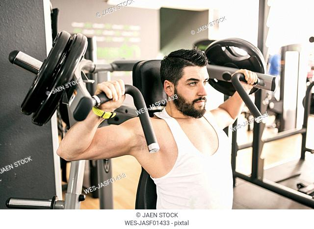 Man exercising with shoulder machine in gym