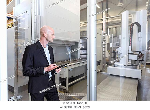 Businessman looking at machine in modern factory