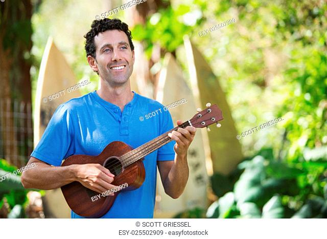 Single handsome male in blue playing ukelele