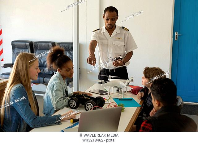 Pilot giving training about model aeroplane to students