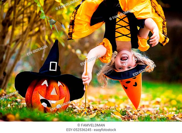 Little girl in witch costume playing in autumn park. Child having fun at Halloween trick or treat. Kids trick or treating