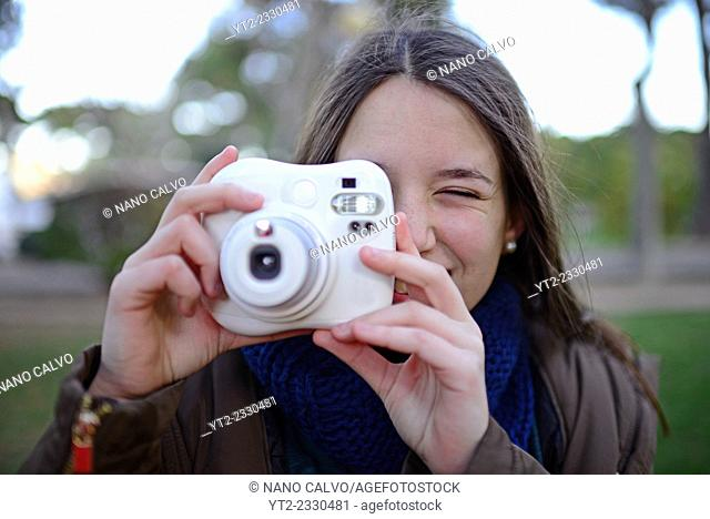 Cute teenager using an instant camera