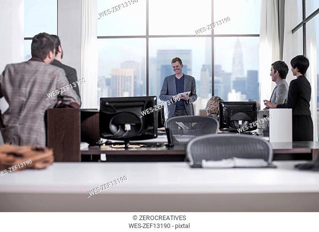 People looking at smiling businessman in city office