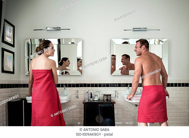 Young couple at sinks in his and hers bathroom