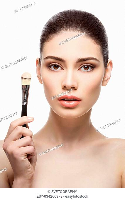 Beautiful girl holding foundation brush. Isolated over white background. Copy space