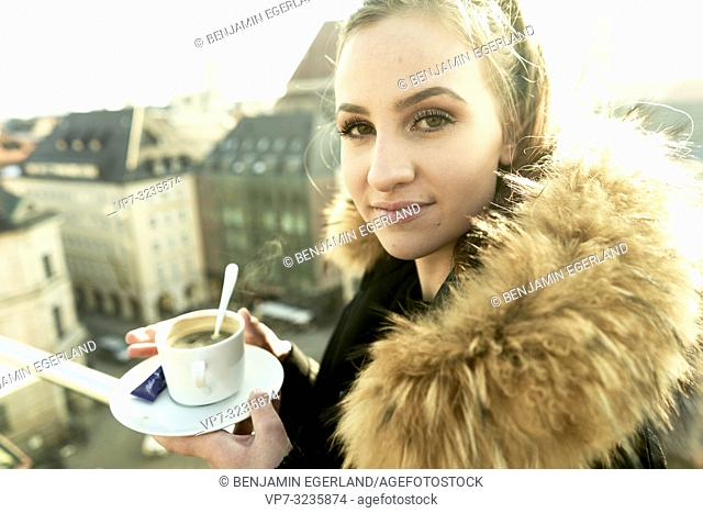 woman holding porcelain coffee cup outdoors in city, wearing winter collar, in Munich, Germany
