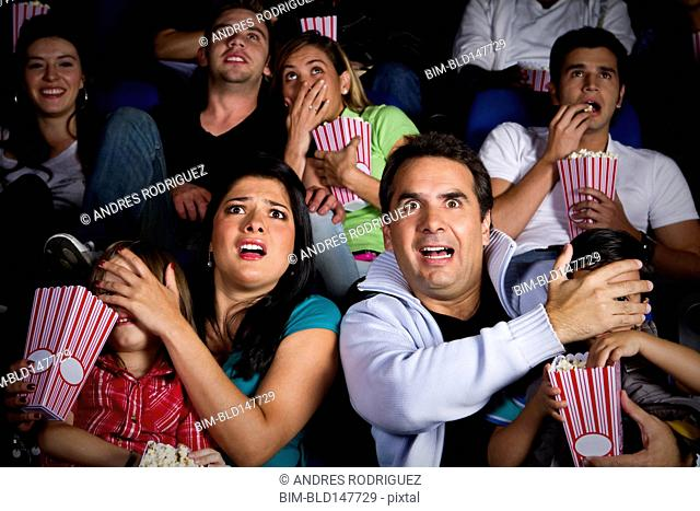 Frightened Hispanic family watching film in movie theater