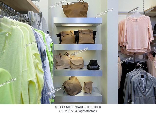 Blouses, shirts hanging on rack in retail shop interior. Bags, handbags, shoulder bags on shelf