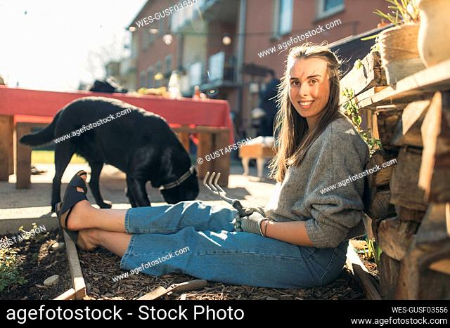 Happy young woman with dog in garden