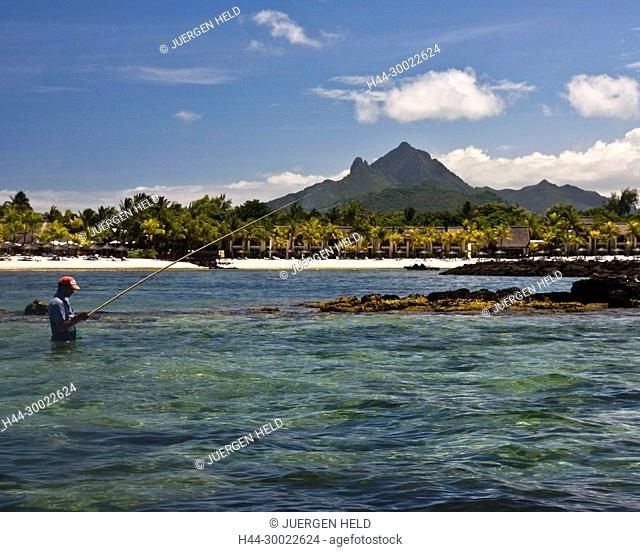 Fisherman, background Villas waterfront of five star Hotel Le Touessrok in Trou d Eau Douce, Mauritius, Africa