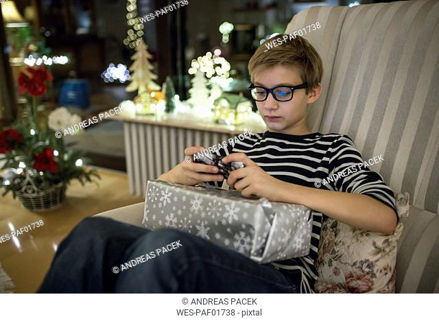 Gift giving at Christmas eve, boy paying with smart phone having present on his lap