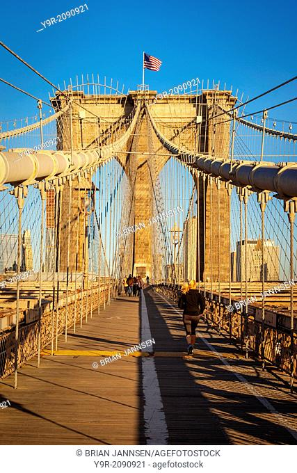Pedestrian pathway along the Brooklyn Bridge with the buildings of the Financial District beyond, New York City, USA