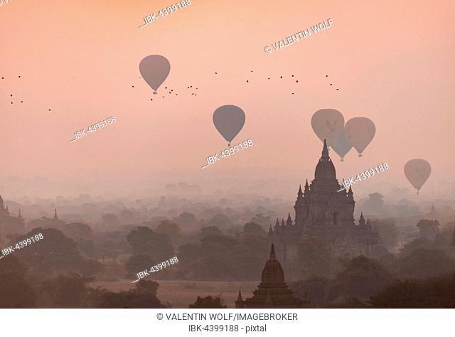 View of pagodas with hot air balloons, temples, sunrise, haze, morning light, Bagan, Division Mandalay, Myanmar