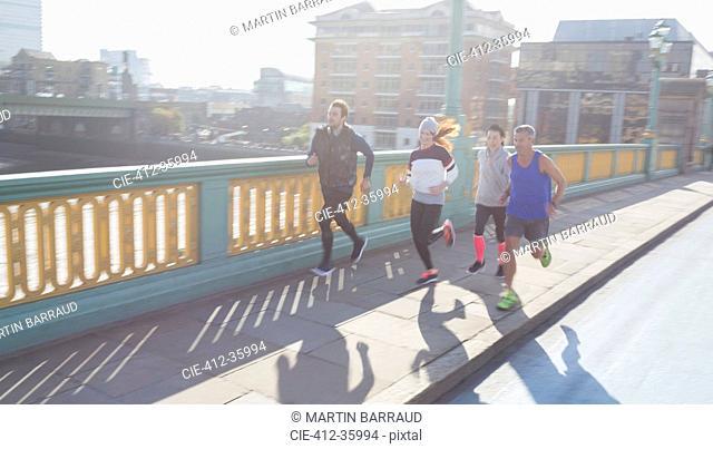 Runners running on sunny urban bridge