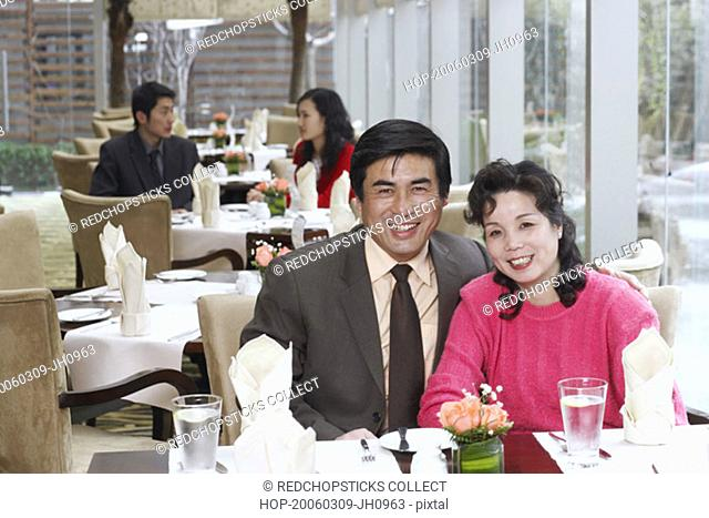 Portrait of a mature couple sitting in a restaurant smiling