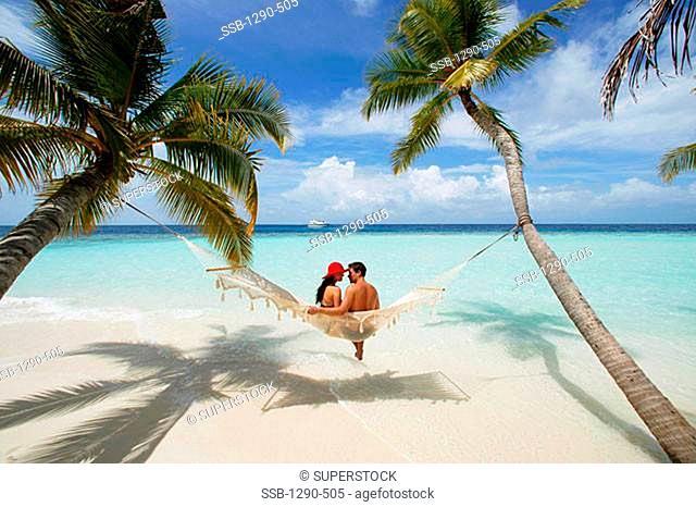 Rear view of a young couple sitting in a hammock, Maayafushi, Maldives