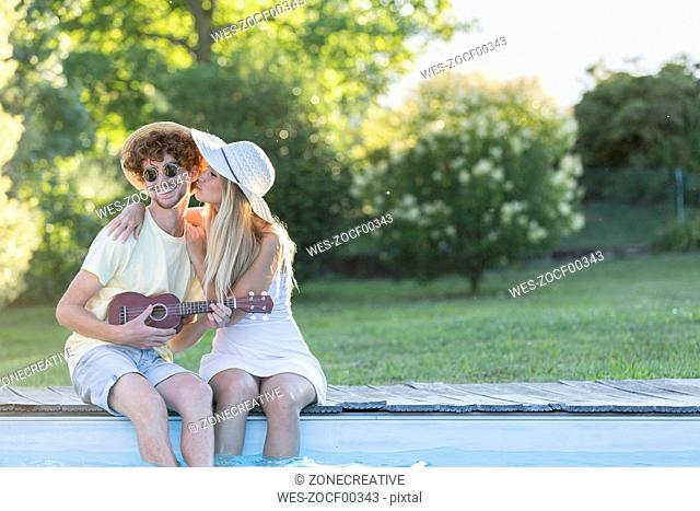 Young couple relaxing at pool edge