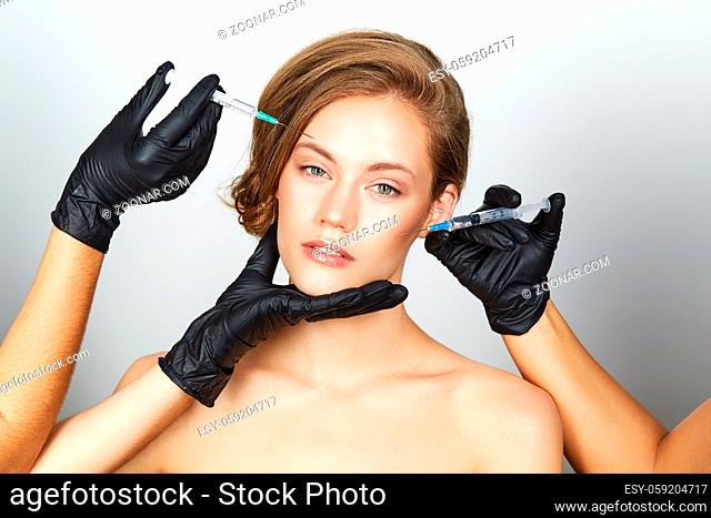 beautiful young woman getting beauty injection. studio shot isolated on white background. copy space