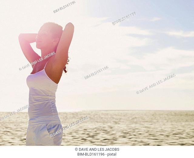 Mixed race woman standing on beach